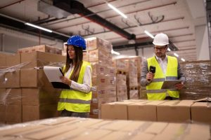 warehouse-workers-using-bar-code-scanner-and-tablet-and-checking-goods-inventory